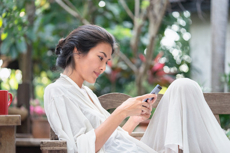 Beautiful young girl in a white dress that using the smart phone. On a wooden chair in the garden. - Relax time concept.