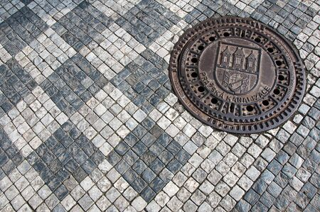 city coat of arms: Sett and sewer manhole with Prague city coat of arms