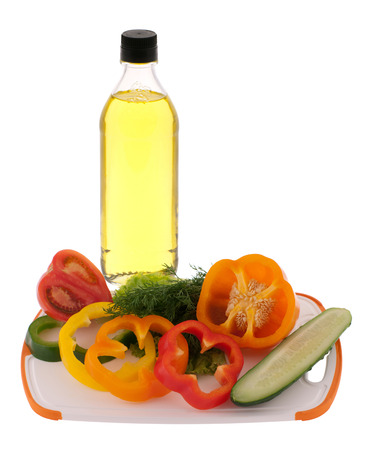 Sliced vegetables at plastic cutting board and a bottle of oil isolated on white photo
