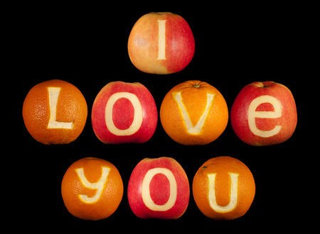 love declaration: Declaration of love carved on apples and oranges isolated on black Stock Photo
