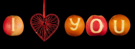 declaration of love: Declaration of love: toy heart and letters carved on oranges and apples Stock Photo