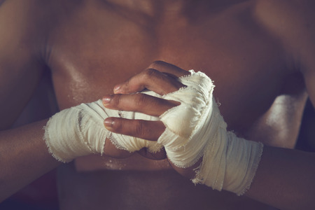 padding: Boxer tape tied around his hand, ready to fight.