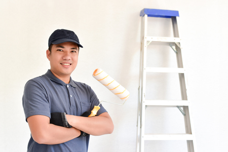 Asian Smiling painter holding a paint roller and backdrop has an aluminum ladder, Portrait of happy mature man looking at camera isolated over White wall. Satisfied handyman with copy space.