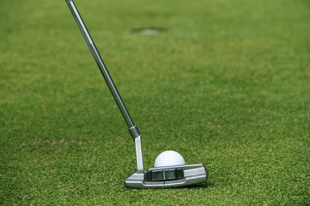 Golfer putting golf ball on the green golf. lens flare on sun set evening time.