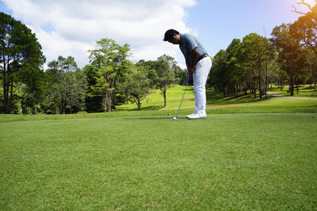 Golfer putting golf in beautiful golf course in the evening golf course with sunshine in thailand 免版税图像