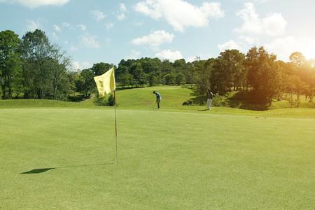 Golfspieler, der Golf auf dem schönen Golfplatz am Abendgolfplatz mit Sonnenschein in thailand spielt