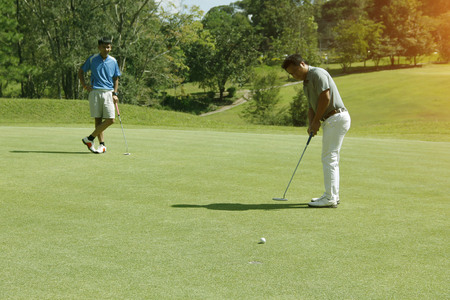 Golfer putting golf in beautiful golf course in the evening golf course with sunshine in thailand Stock Photo