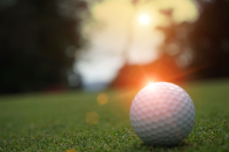 Blurred golf ball in beautiful golf course with sunset. Golf ball close up in golf coures at Thailand