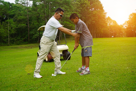 Man teaching Asian young to play golf while standing on field. Personal trainer giving lesson on golf course. 스톡 콘텐츠