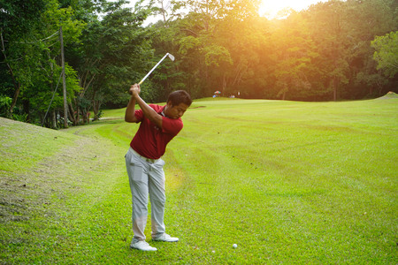 Blurred golfer playing golf in beautiful golf course in the evening golf course with sunshine in thailand