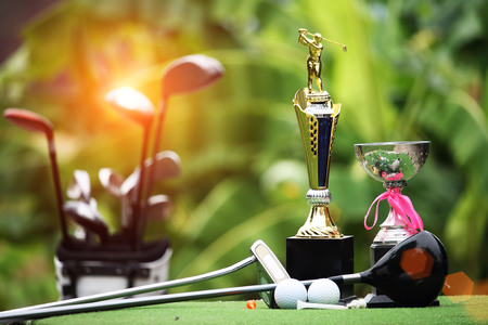 Collection of golf equipment resting on green grass with green background