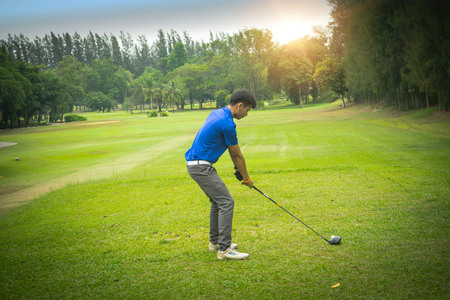 Golfer golfen in de avond golfbaan, op zonsondergang avond tijd. Man golfen op een golfbaan in de zon.