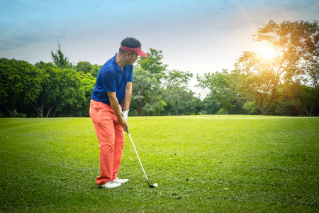 Golfer playing golf in the evening golf course, on sun set evening time. Man playing golf on a golf course in the sun. 免版税图像