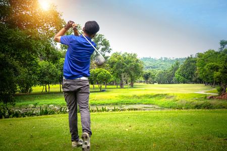 Golfer grający w golfa wieczorem pole golfowe, o zachodzie słońca wieczorem. Mężczyzna gra w golfa na polu golfowym w słońcu.