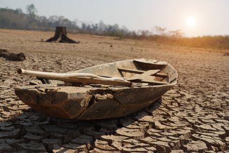 Fishing boat on drought conditions. The drought land texture in Thailand. The global shortage of water on the planet.