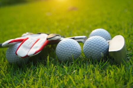 Golf equipment. Golf ball and golf club on green grass background.