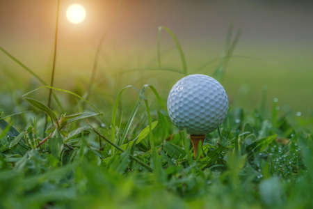 Closeup golf ball on tee ready to be shot. Golf ball on tee in the evening golf course with sunshine. Blurred set of golf clubs over green field background. Stock Photo