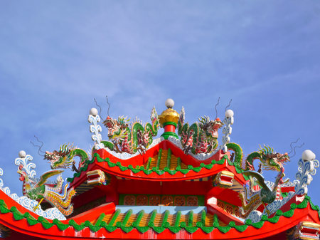 china dragon and phoenix bird statue and gold lotus lamp on the roof of octagon pavilion and blue sky Stock Photo