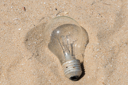 burnt out: Old Tungsten lamp on the sand Stock Photo