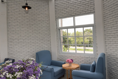 loft living: blue classic armchair in modern loft living room with white brick wall Stock Photo