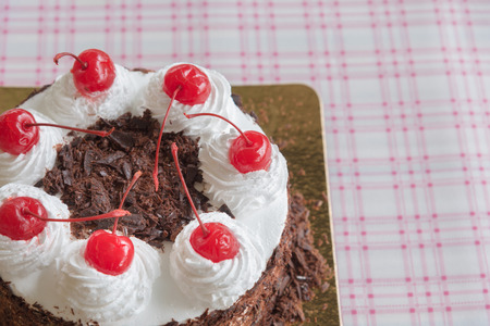 Black forest cake decorated with whipped cream and cherries Stock Photo
