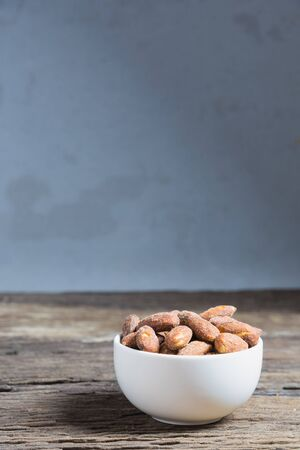 salted: Salt roasted almond in white bowl on wooden table