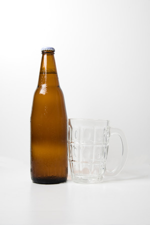 intoxicate: Brown beer bottle With empty beer glass on white background