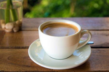 cup of fresh coffee with coffee beans on wooden table Stock Photo