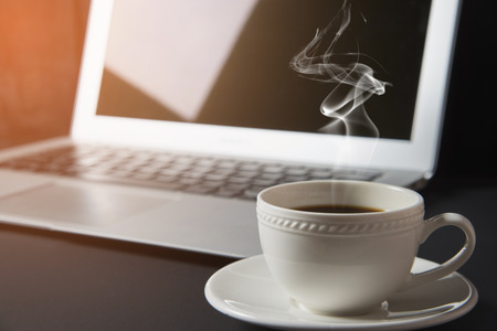 cup of coffee and laptop on the table