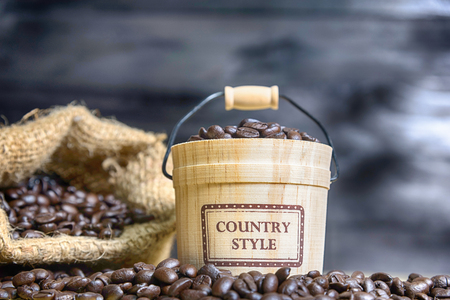 Coffee beans with casks on wood background Stock Photo