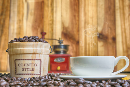 Coffee cup and Coffee beans with casks on wood background Stock Photo