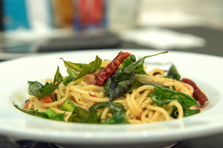 Spicy spaghetti with bacon and basil in the white dish.