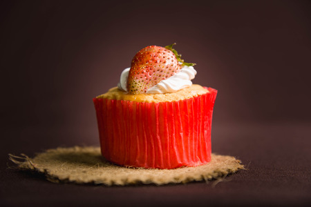 red velvet cupcake: cup cake strawberry on brown background Stock Photo