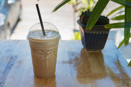 Cappuccino frappe in plastic cup. Take away package. Easy cup. Refreshment drink. On white table. Stock Photo