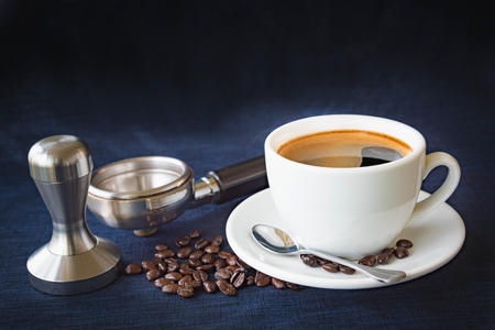 Coffee cup and beans with Equipment for coffee on a dark blue fabric background