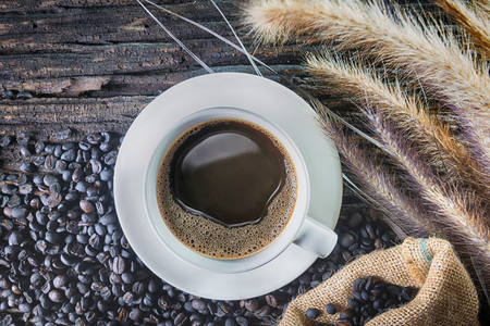 crema: Coffee cup and beans on wooden table Stock Photo