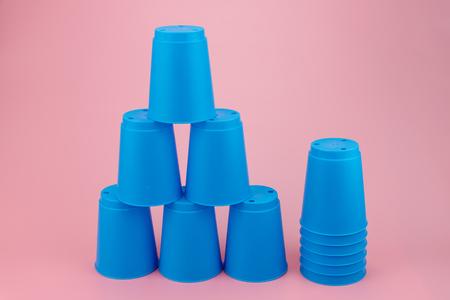 blauwe stapels plastic bekers. Snelheid stapel cup op roze achtergrond