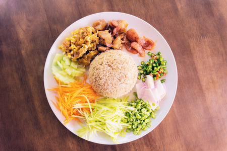 KA: Rice Seasoned with Shrimp Paste, Thai food on white dish over wooden table. khaao khlook gabpi. Kao Cluk Ka Pi,