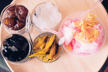 Shaved ice. Frozen Fruit Slush Drinks,Shaved Ice dessert on wood plate, Mix dessert Stock Photo