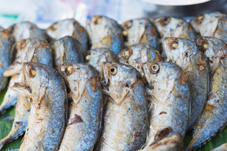 fish vendor: Fried shortbodied mackerel fish, Thai style fried mackerel or Pla Two a traditional Thai Cuisine on side street food vendor often served Stock Photo