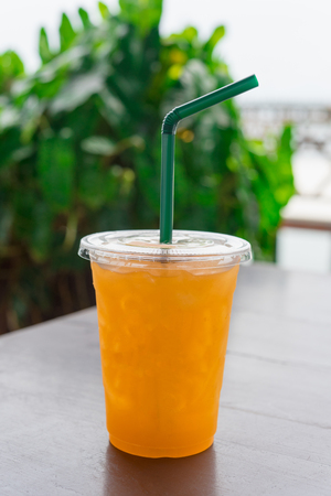Orange juice  in a plastic glass placed on a wooden table.Fresh orange juice with straw and slice in take away cup.