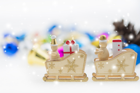 Santa Claus in a sleigh with gift and sock, all in wood Stock Photo