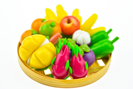 Fruits and vegetables make a small imitation on white background. miniature figure many fruit on the plate.