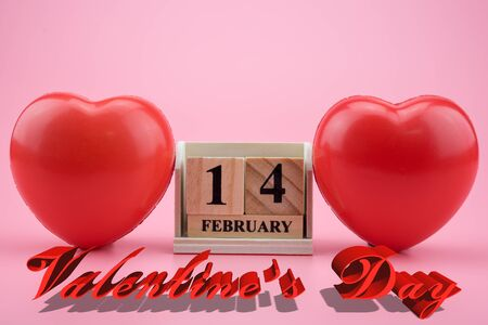 red hearts with Wooden calendar on pink background. Valentines day card concept. Heart for Valentines Day Background. Stock Photo
