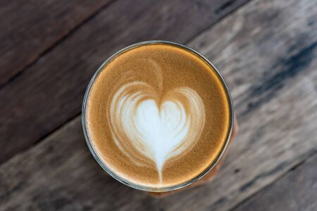 Late art coffee with heart shape on wood table background.