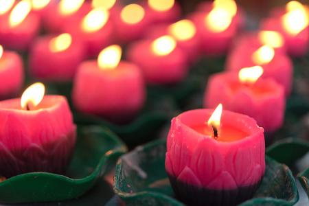 Candle in front of many defocused candle flames. Flower candles burning at night. Many burning candles with shallow depth of field. Foto de archivo