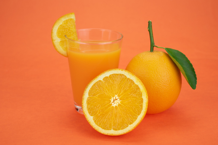Glass of fresh orange juice with group of orange on orange color background with copy space. Orange juice and oranges with leaves on orange background 免版税图像
