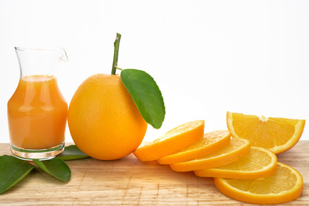 Glass of fresh orange juice with group of orange on white background with copy space. Orange juice and oranges with leaves on isolate background