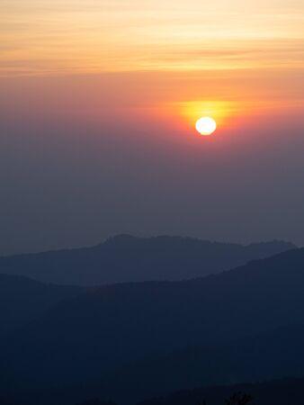 Paisaje de montañas. espectacular puesta de sol sobre el cielo nublado. el fuerte amanecer con un rayo plateado y una nube en el cielo naranja