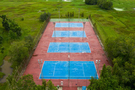Aerial view of tennis court empty in countryside, A tennis court behind a wire fence, netting up by nobody playing,